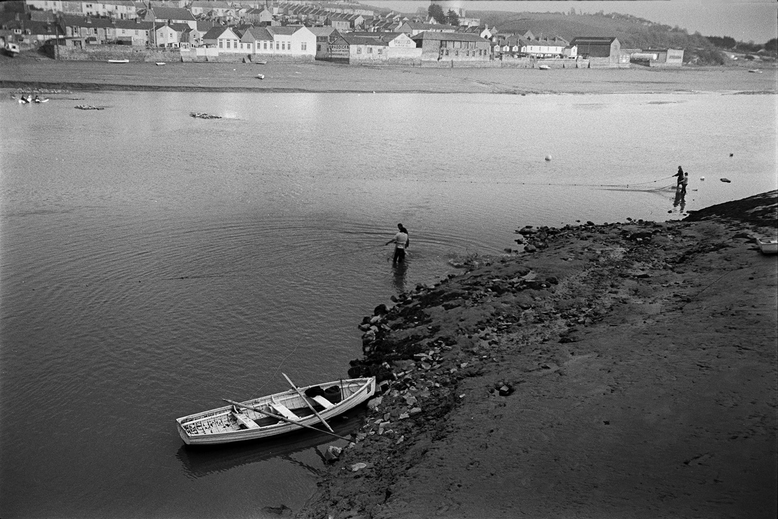 People pulling in salmon nets on the River Torridge at Bideford. A rowing boat is moored by the river bank. Houses in the town are visible opposite the river.