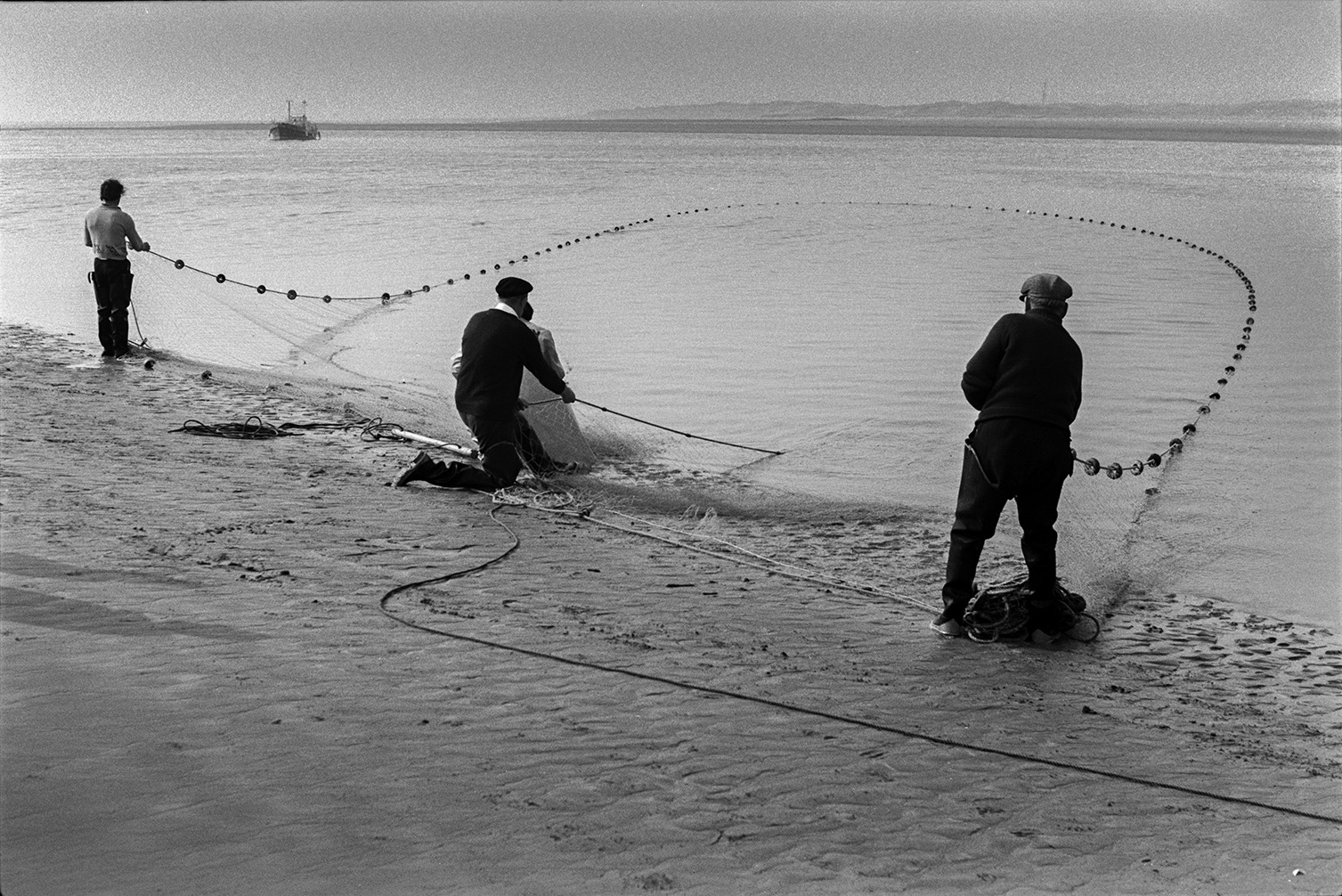 Men netting salmon on the beach front at Appledore. A ship can be seen in the background.