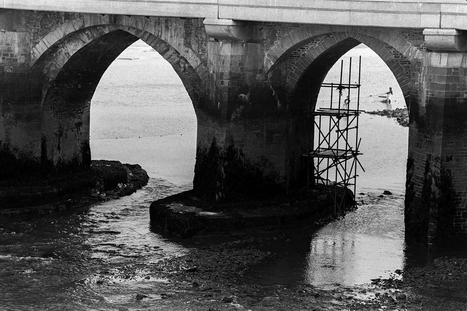 Scaffolding on one of the arches of Bideford Long Bridge, also known as Bideford Old Bridge. People can be seen netting salmon in the River Torridge through one of the bridge arches.