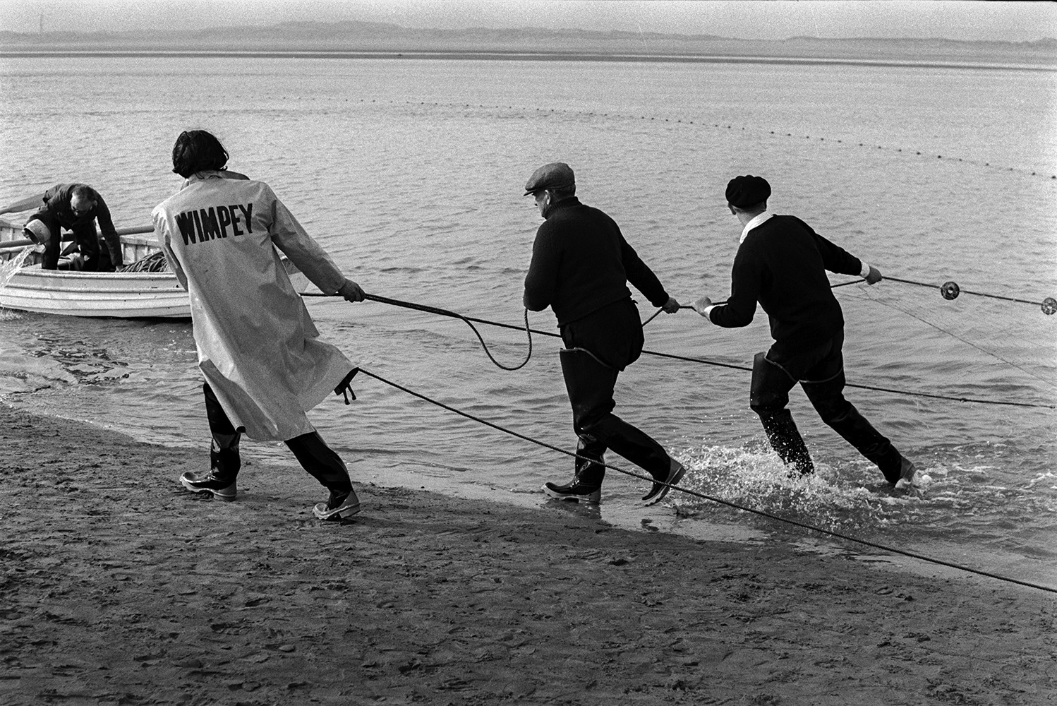 Men hauling in a large fishing net, possibly at Appledore. One of them is wearing a coat with the word'Wimpey' written on the back. Another man is in a rowing boat nearby. Land can be seen on the horizon.