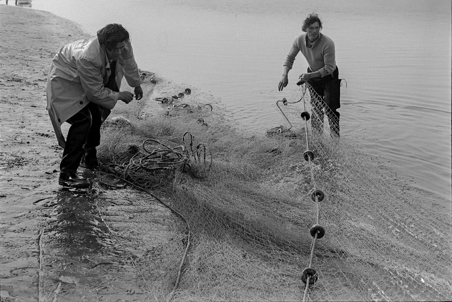 Two men hauling in a large fishing net, possibly at Appledore.