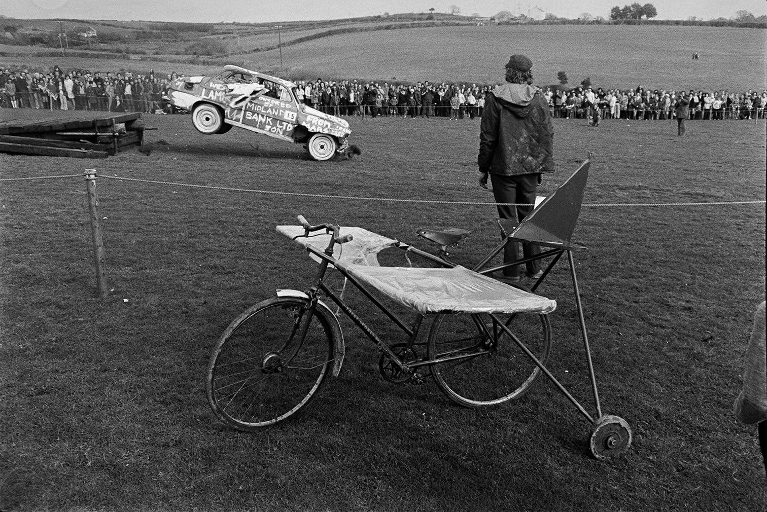A'Man Powered Flight' competition in a field at Crowbeare. A person is watching a car trying to fly off a ramp. In the foreground an adapted bicycle with wings is waiting to compete.