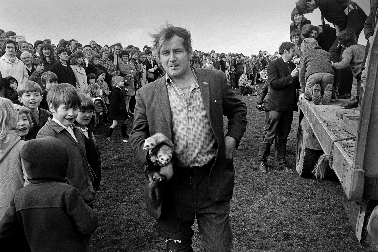 A man holding two ferrets in front of a crowd of spectators at a'Man Powered Flight' competition in a field at Crowbeare. Children are looking at the ferrets and the man is smoking a cigarette.