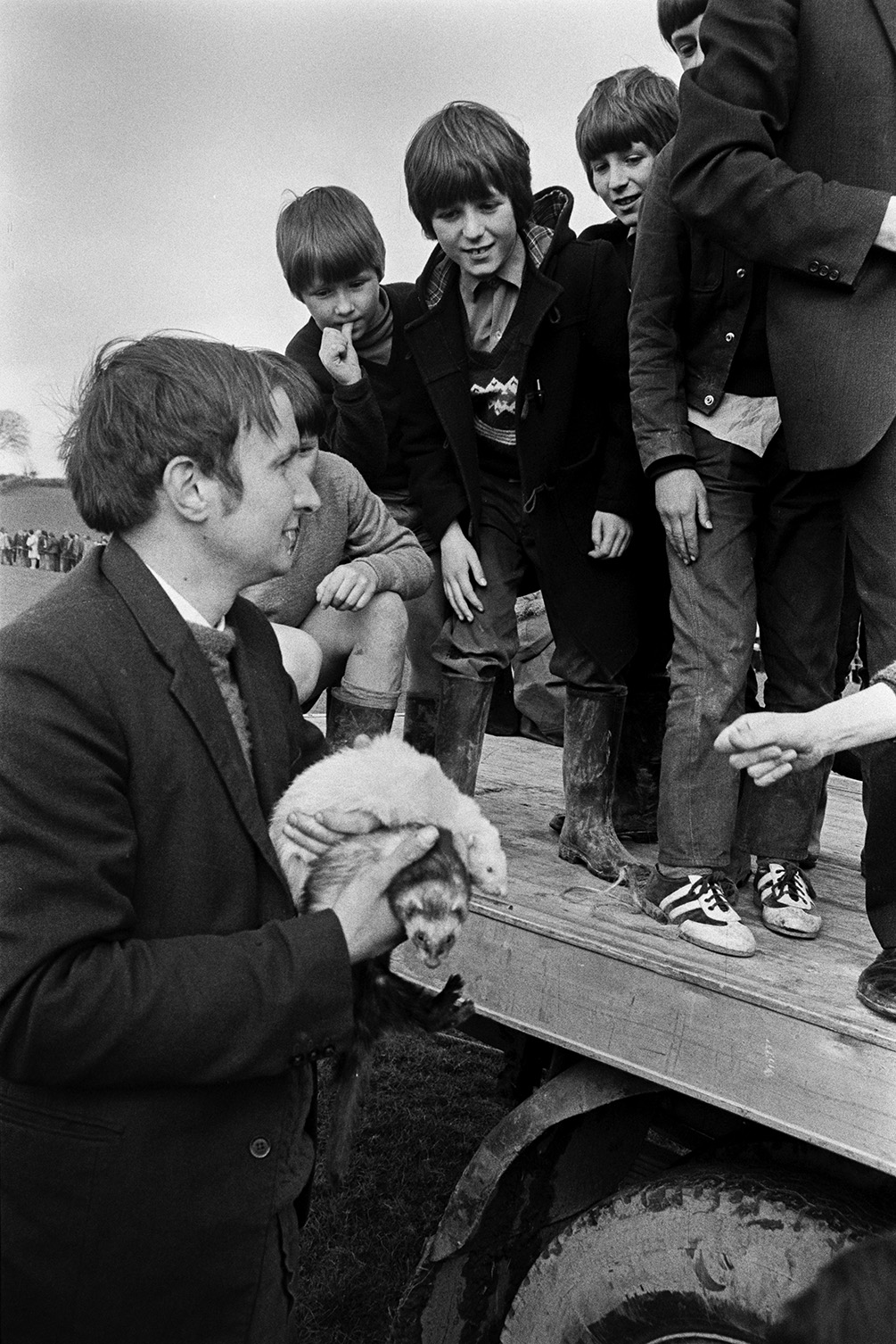 A group of boys stood on a trailer and reaching out to stroke two ferrets which a man is holding, at a'Man Powered Flight' competition in a field at Crowbeare.