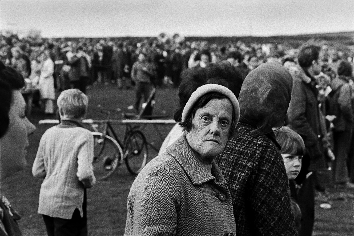 Spectators, including men, women and children, at'Man Powered Flight' competition in a field at Crowbeare. A woman is looking over her shoulder in the foreground.