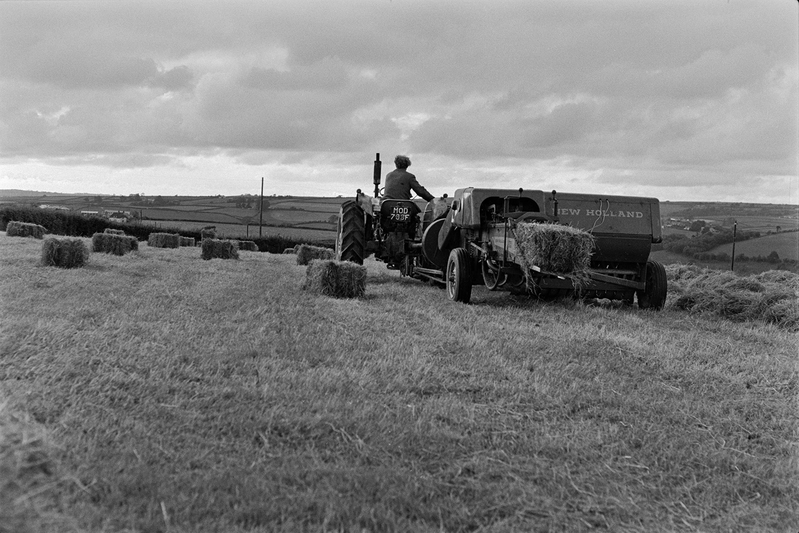 Ivor Bourne driving a tractor and baler in a field at Mill Road Farm, Beaford. A hay bale can be seen coming out of the baler. The farm was also known as Jeffrys.