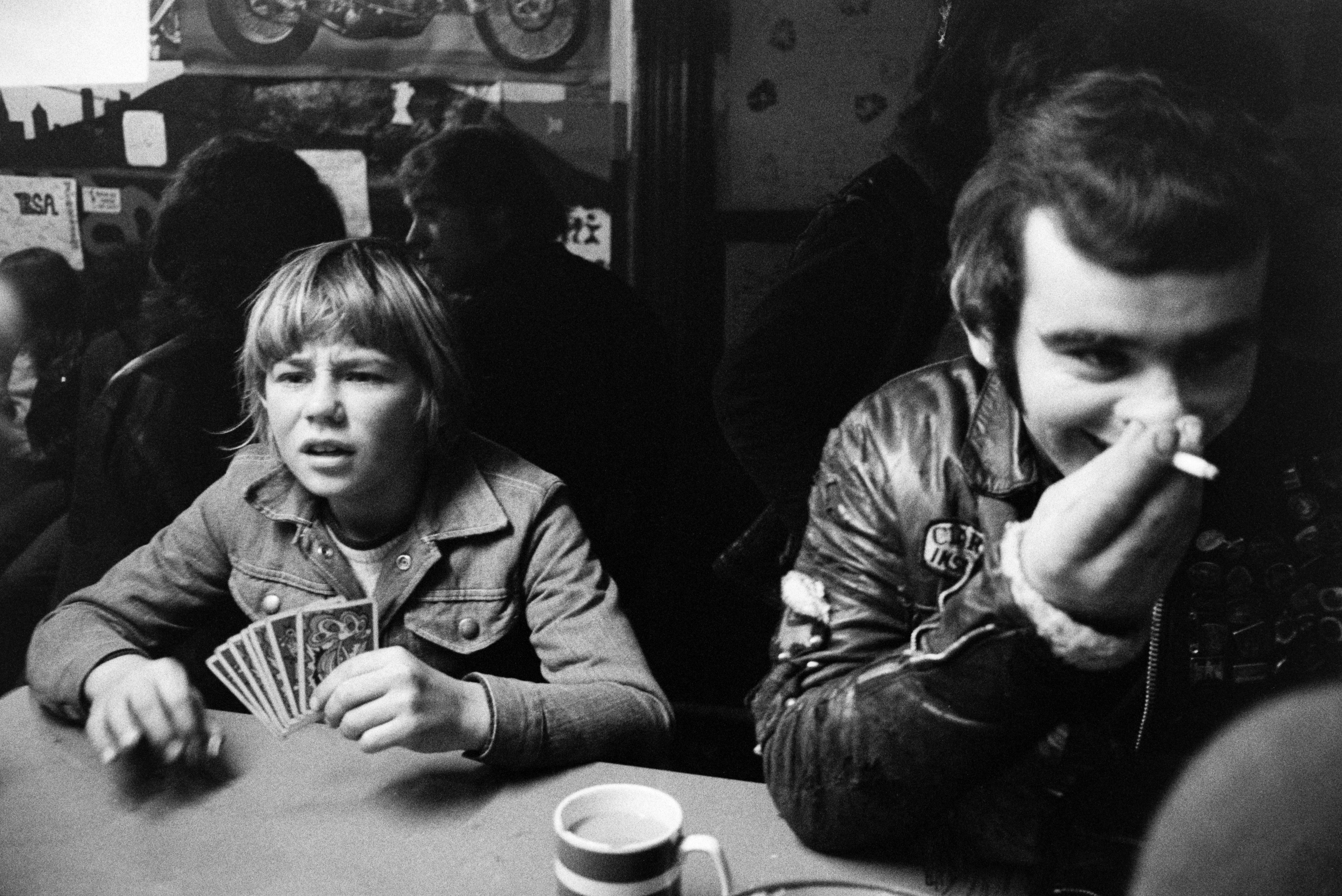 A young man and boy playing cards at a table, possibly in a pub, youth club or cafe. The young man is smoking and wearing a leather jacket.