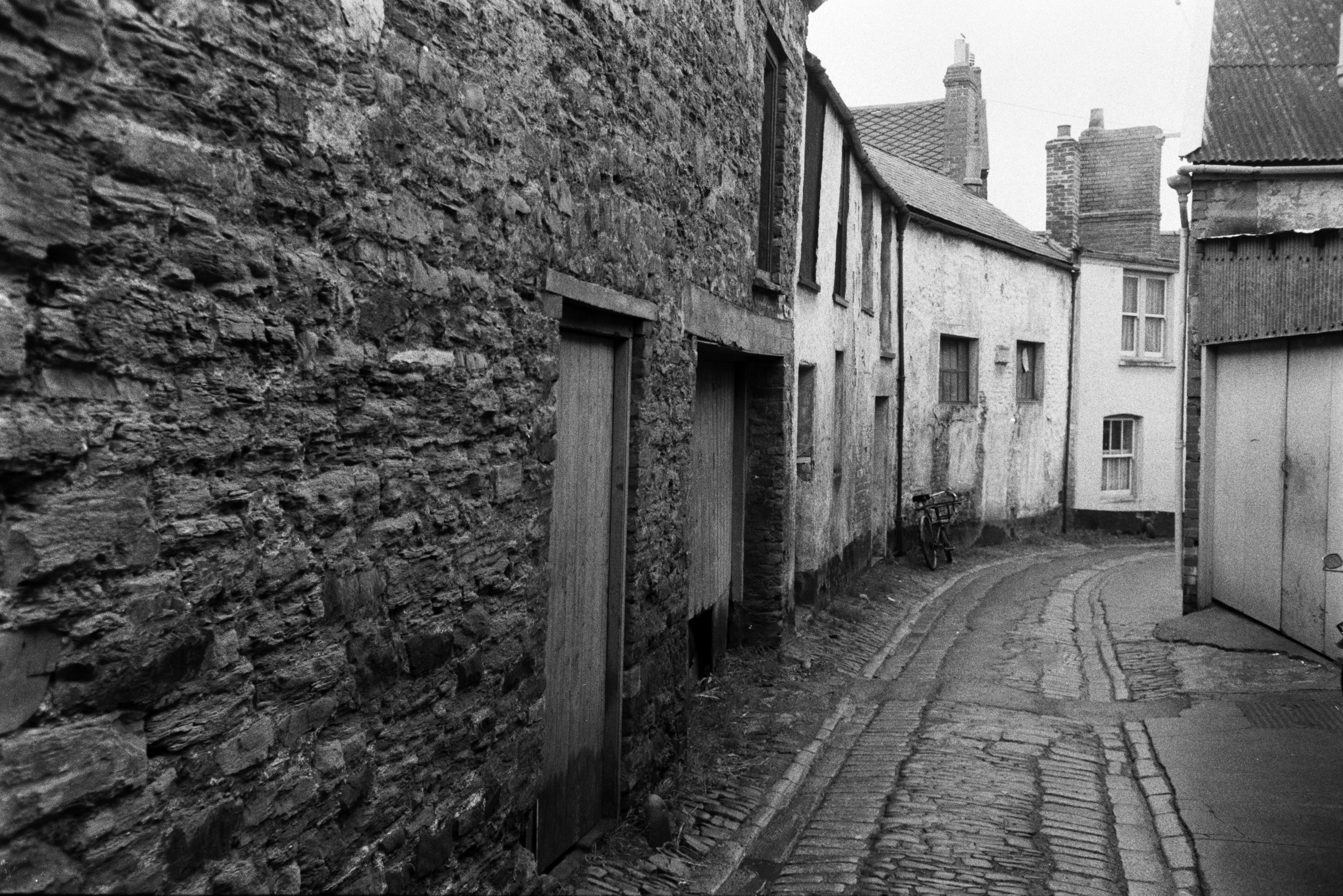 A narrow cobbled street with terraced houses in Barnstaple. A bicycle is parked outside one of the houses.