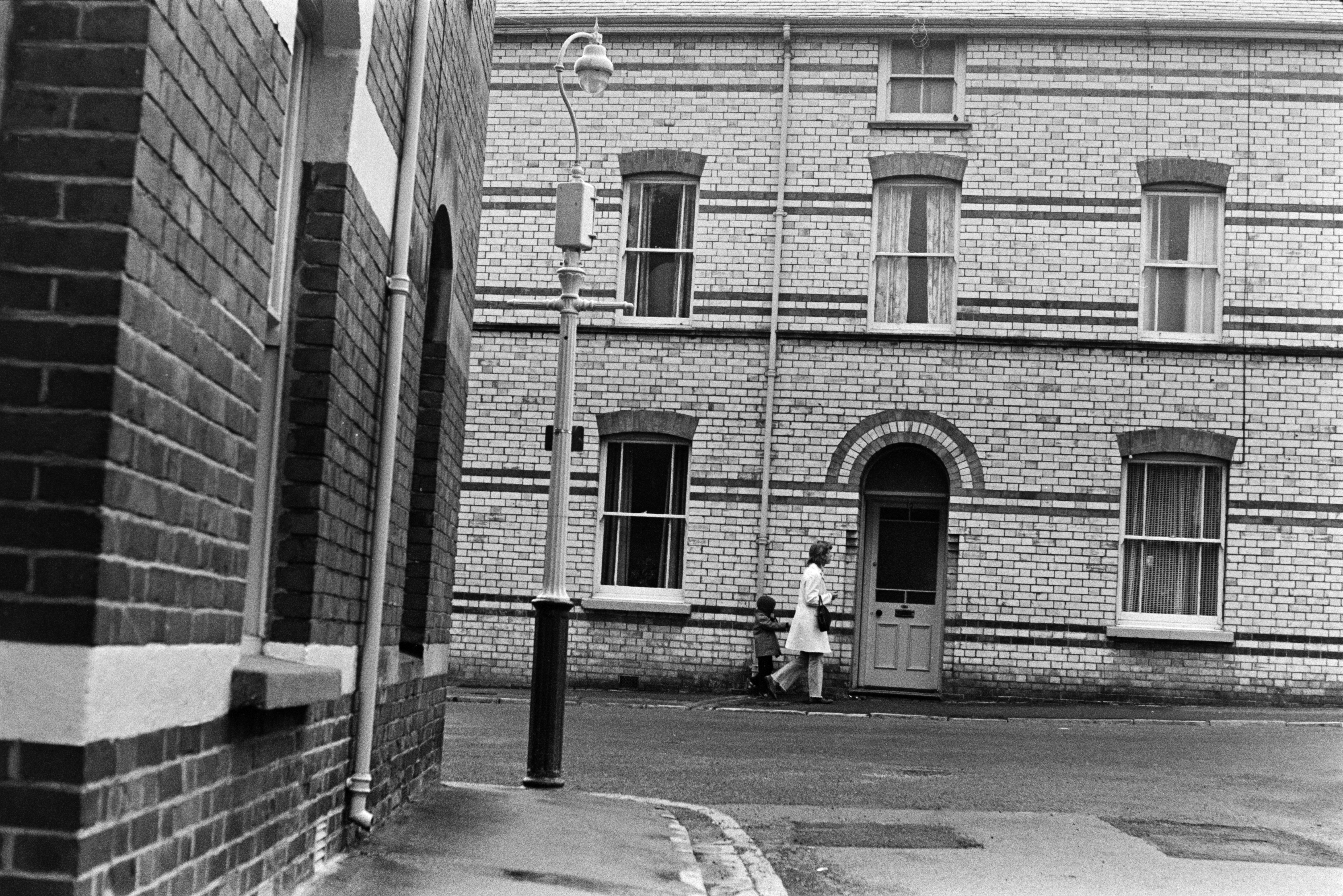 A woman and child walking down a street with terraced brick houses in Barnstaple. The door and window lintels are arched and a lamppost is on the street corner.