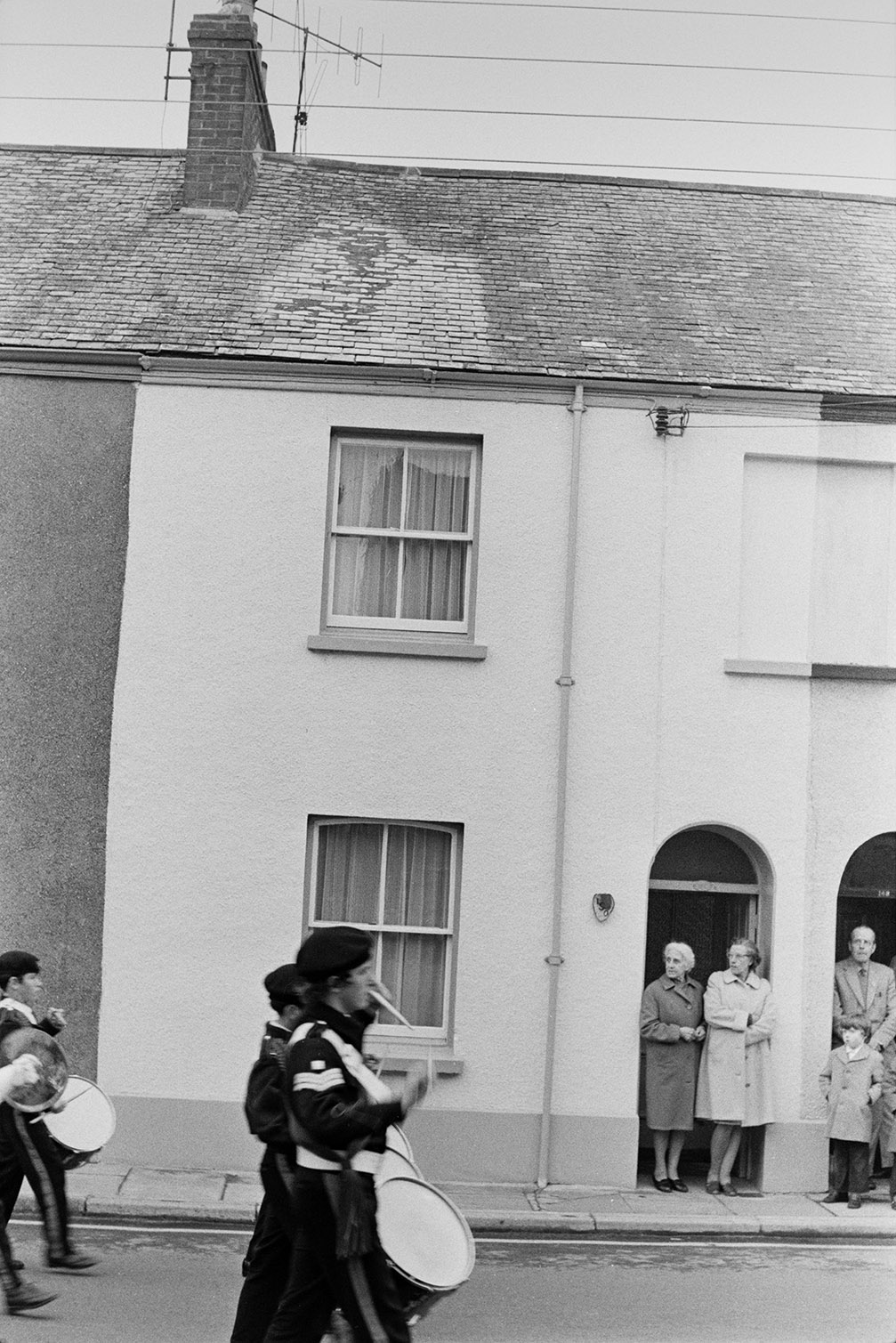 A band of drummers marching in the Torrington May Fair parade. Women, a man and a child are watching from the doorways of their houses in Torrington.