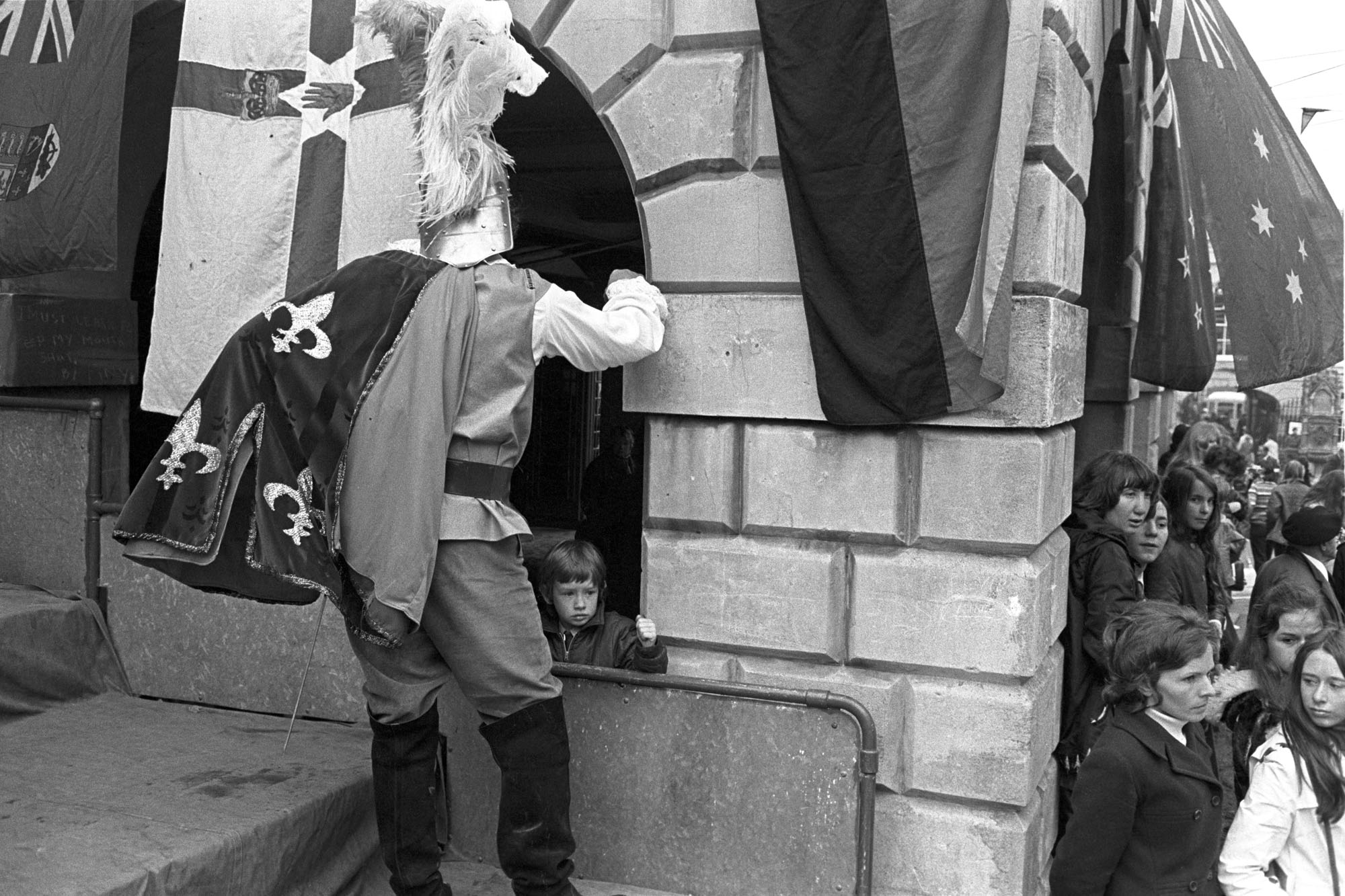 Torrington May Fair. Crowds and performers in High Street.<br /> [People at Torrington May Fair in Torrington High Street. A person dressed as a knight looking into an archway partially covered by a flag, (possibly part of the Town Hall). A child is peering out of the archway.]