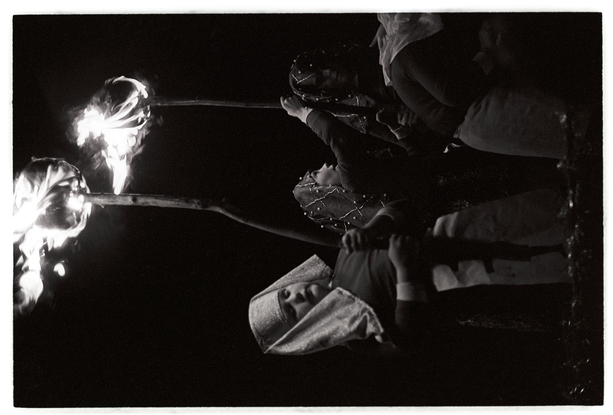 Boys with flaming torches at night.<br /> [Children carrying flaming torches with the 'Tutankhamun' carnival float at Dolton Carnival.]