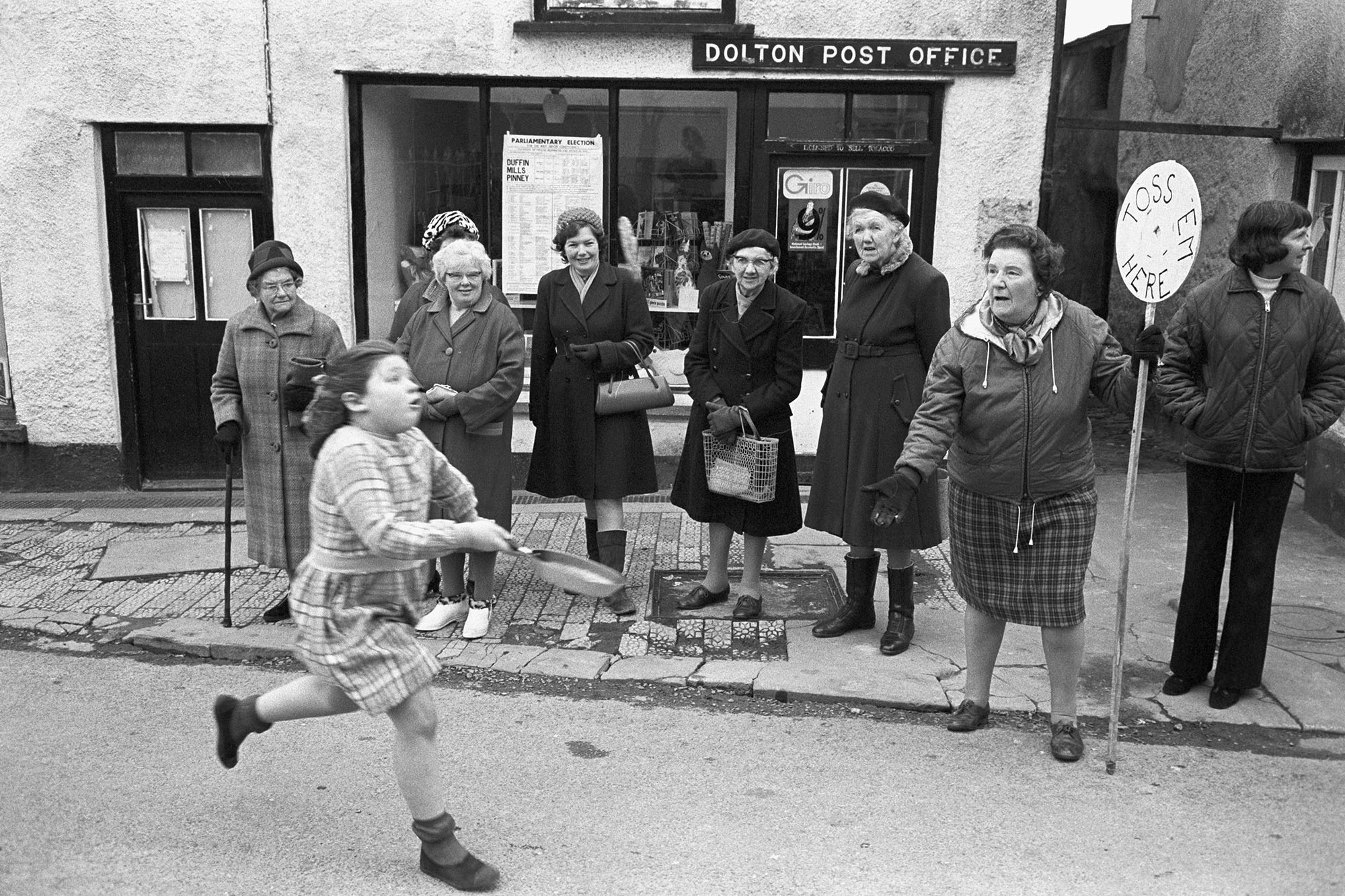 Pancake race, runner and spectators outside Post Office.<br /> [Spectators watching Diane Hiscock running in the pancake race outside Dolton Post Office. A woman with a 'Toss Em Here' sign is also outside the Post Office.]