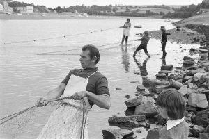 Fishermen hauling salmon nets by James Ravilious