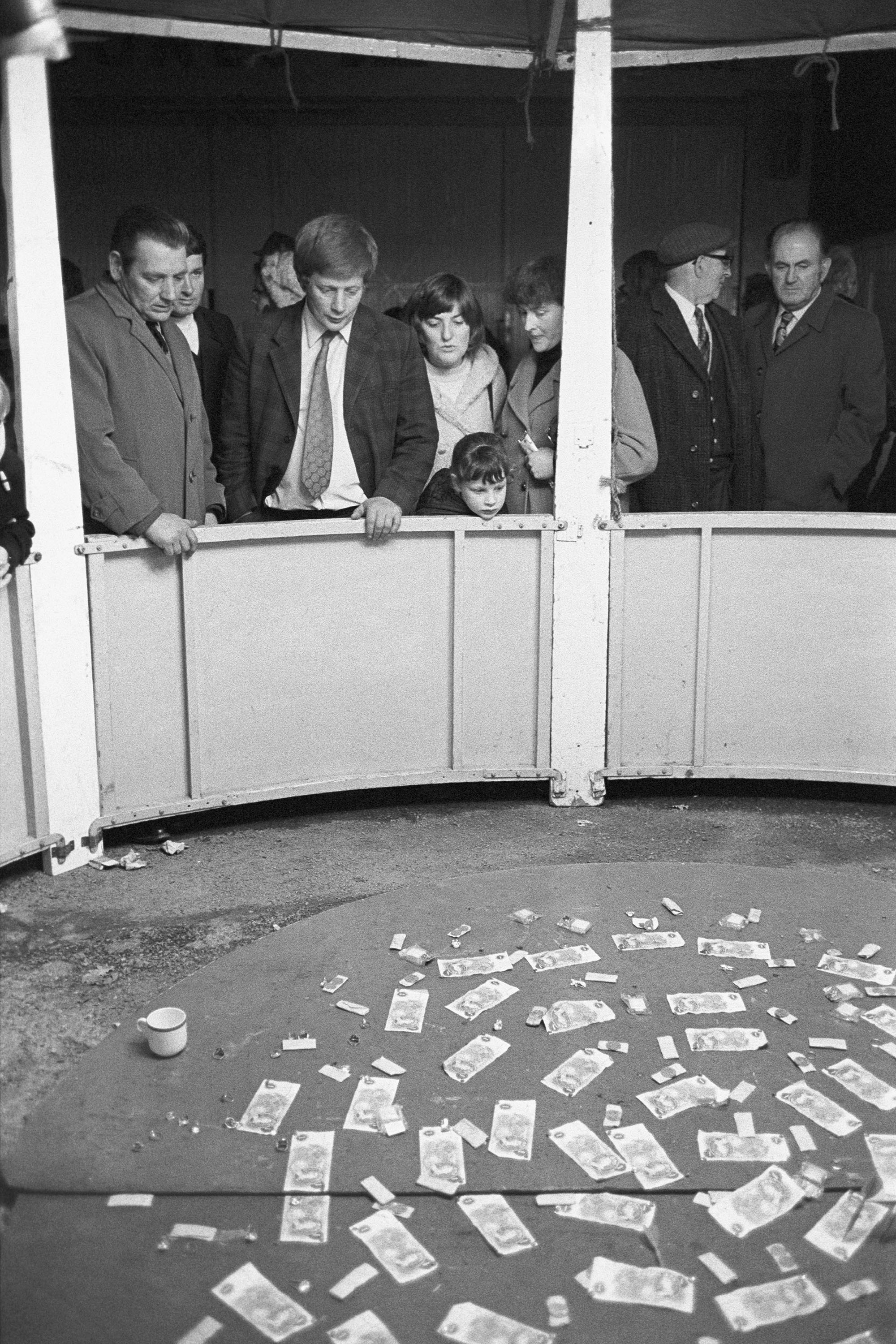 Money stall at Carnival Fair.<br /> [People looking down at a circle of bank notes on the ground in front of them on the money stall at Hatherleigh Carnival.]