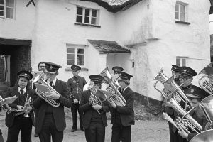 Hatherleigh Silver Band playing outside the Duke of York pub by James Ravilious