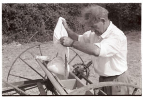Frank Pickard filling a seed drilll by James Ravilious