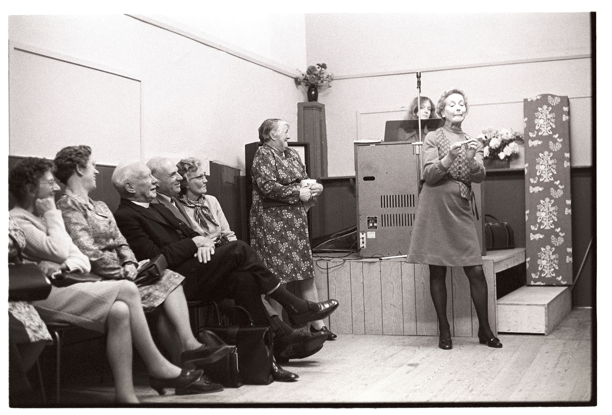 Entertainment at Harvest Supper in village hall.<br /> [Reverend Wallington and other people watching Mrs Wallington perform a mime to entertain people at the Harvest Supper at Roborough Village Hall. A woman is stood up laughing by a small stage.]