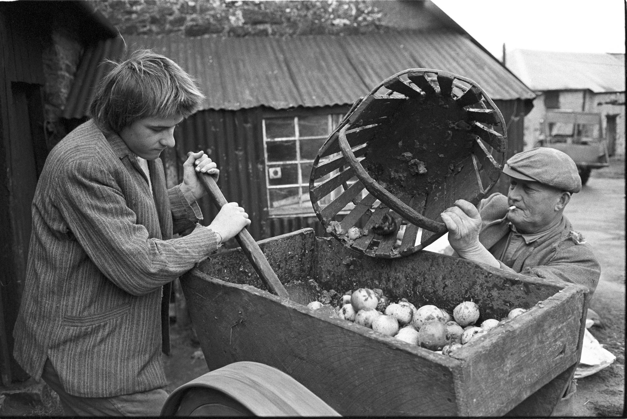 Men using apple crusher.<br /> [Mr Eastman and another man using an apple crusher at Hacknell, Burrington. One man is loading it with a trug of apples, the other is pushing the apples through the crusher.]