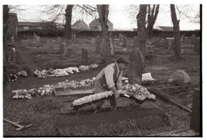 Reginald Rice tidying a grave in Beaford churchyard by James Ravilious