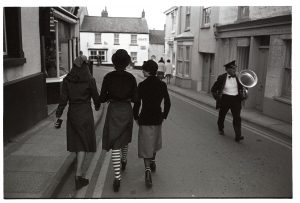Revellers and bandsman before the May Fair parade by James Ravilious