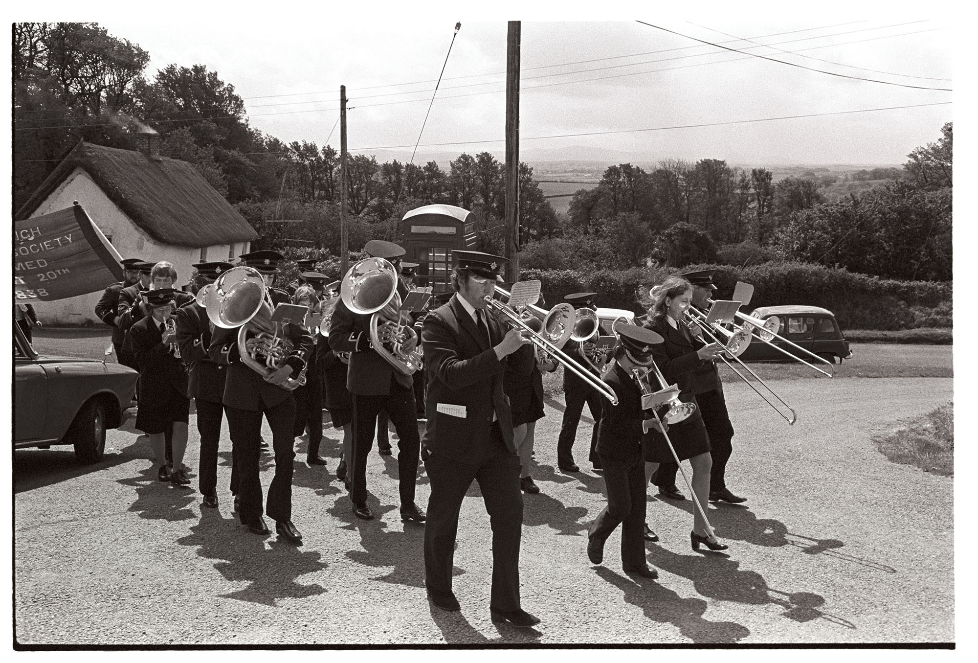 Friendly Society start of parade with Silver Band.<br /> [Hatherleigh Silver Band marching up a road in Iddesleigh for Iddesleigh Club Day. People holding the Iddesleigh Friendly Society banner are following them.]