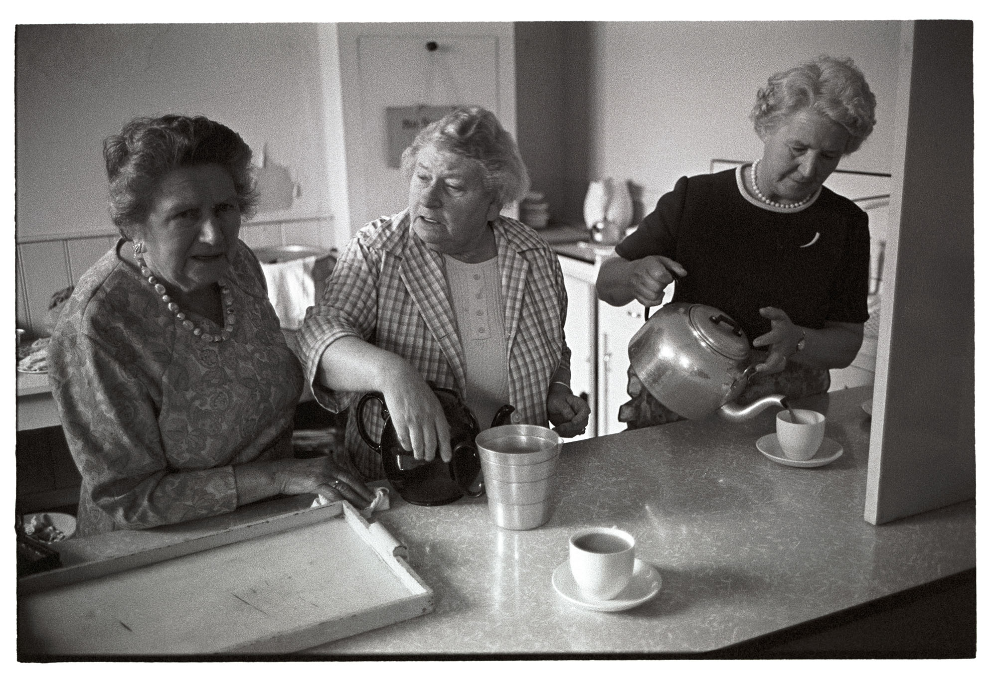 Three women serving tea in old school after parade.<br /> [Three women making tea and chatting at a serving hatch, after the Church Sunday School Parade in Hatherleigh.]