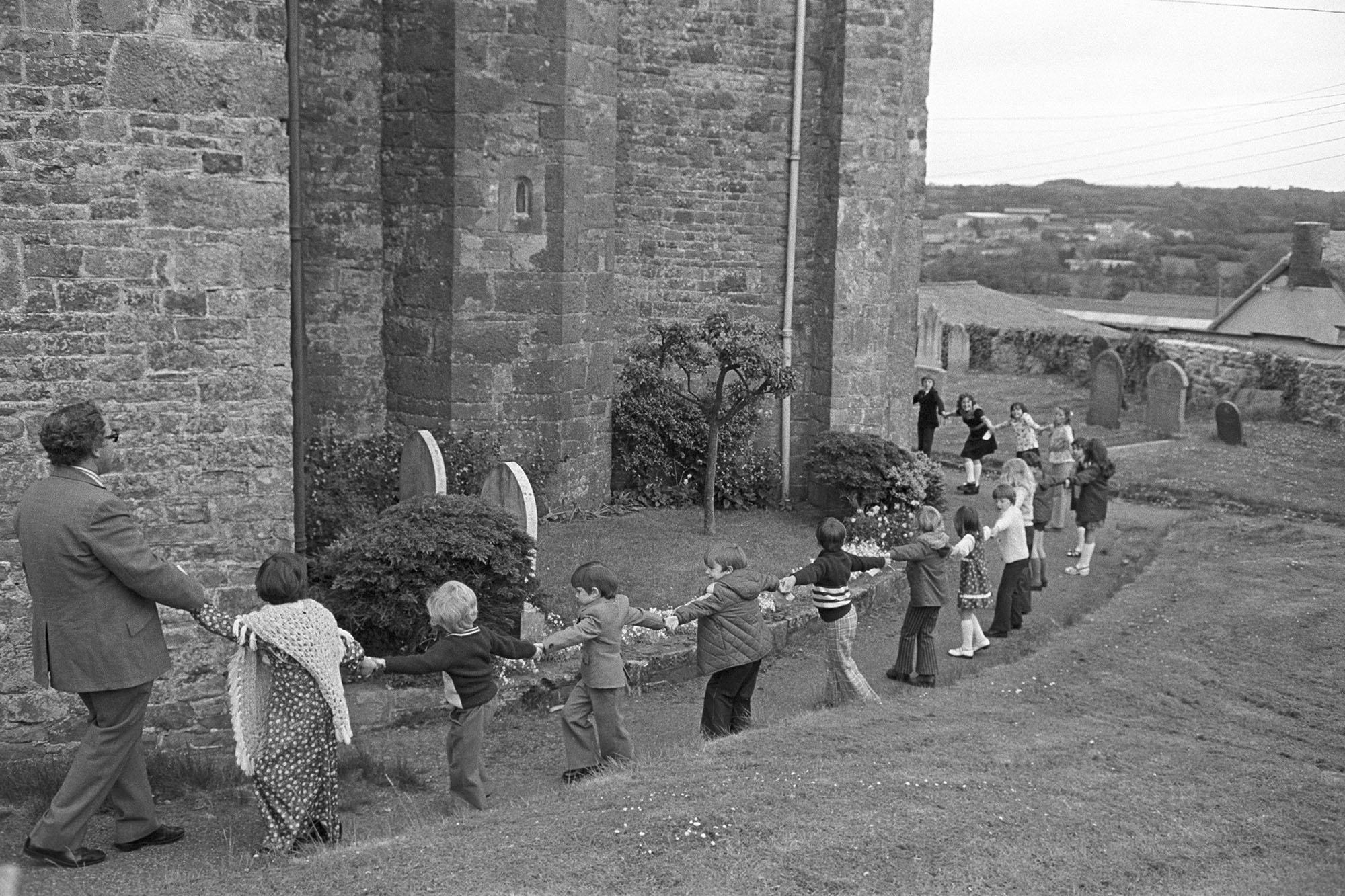 Girdling church after parade Headmaster pulling.<br /> [Charles Tucker with children holding hands around Hatherleigh church for the Church Sunday School Parade.]