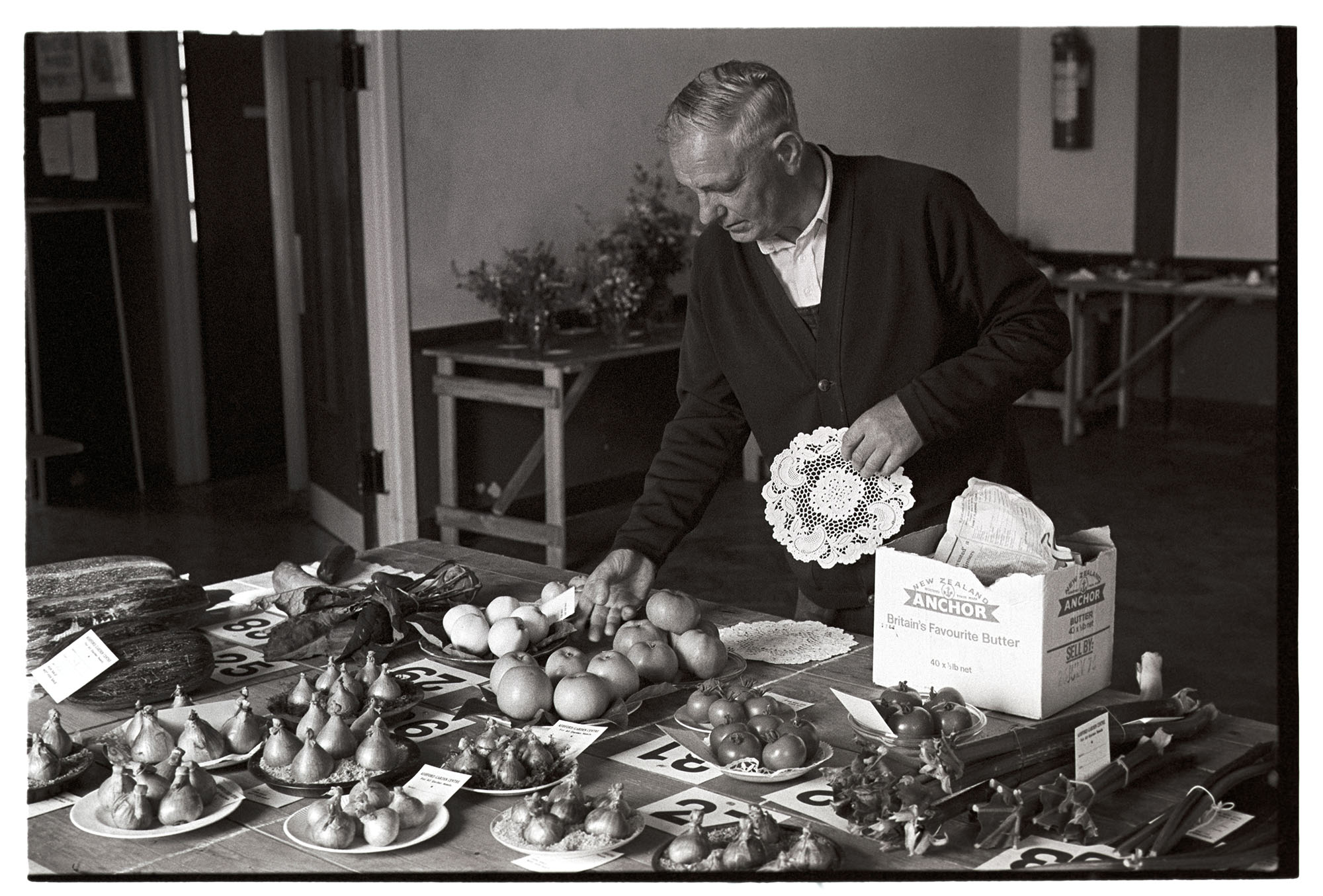 Man laying out produce at Flower Show in village Hall. Fruit, vegetables.<br /> [Philip George holding a doily and laying out produce at the Flower Show in Dolton Village Hall. Onions, apples, marrows and rhubarb are visible on the table.]