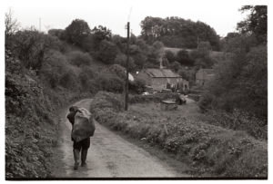 Ivor Brock carrying a sack of logs by James Ravilious