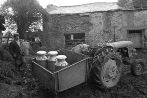 Churns in a tractor link box by James Ravilious