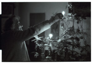 Jean Pickard lighting Christmas tree candles by James Ravilious