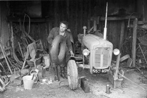 Cyril Dunn mending a puncture by James Ravilious