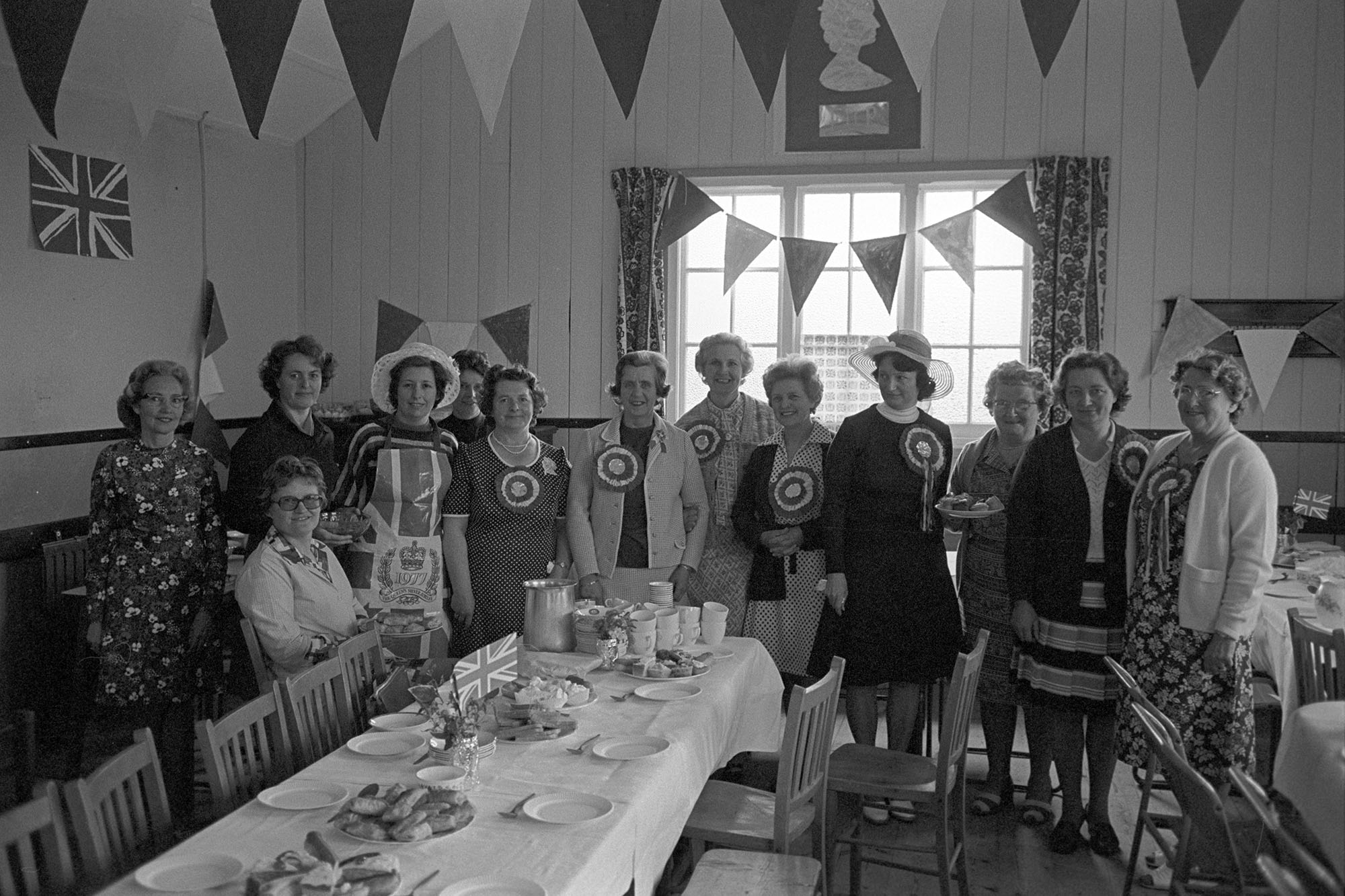 Group of women, in village hall before Jubilee tea which they had prepared.<br /> [Women in High Bickington village hall standing by the tea they have prepared for the Silver Jubilee of Queen Elizabeth II. The tables are laid with cakes and sandwiches and the hall is decorated with bunting and union jack flags. Some of the women are wearing rosettes.]