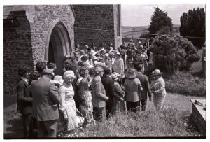 Wedding guests outside the church by James Ravilious