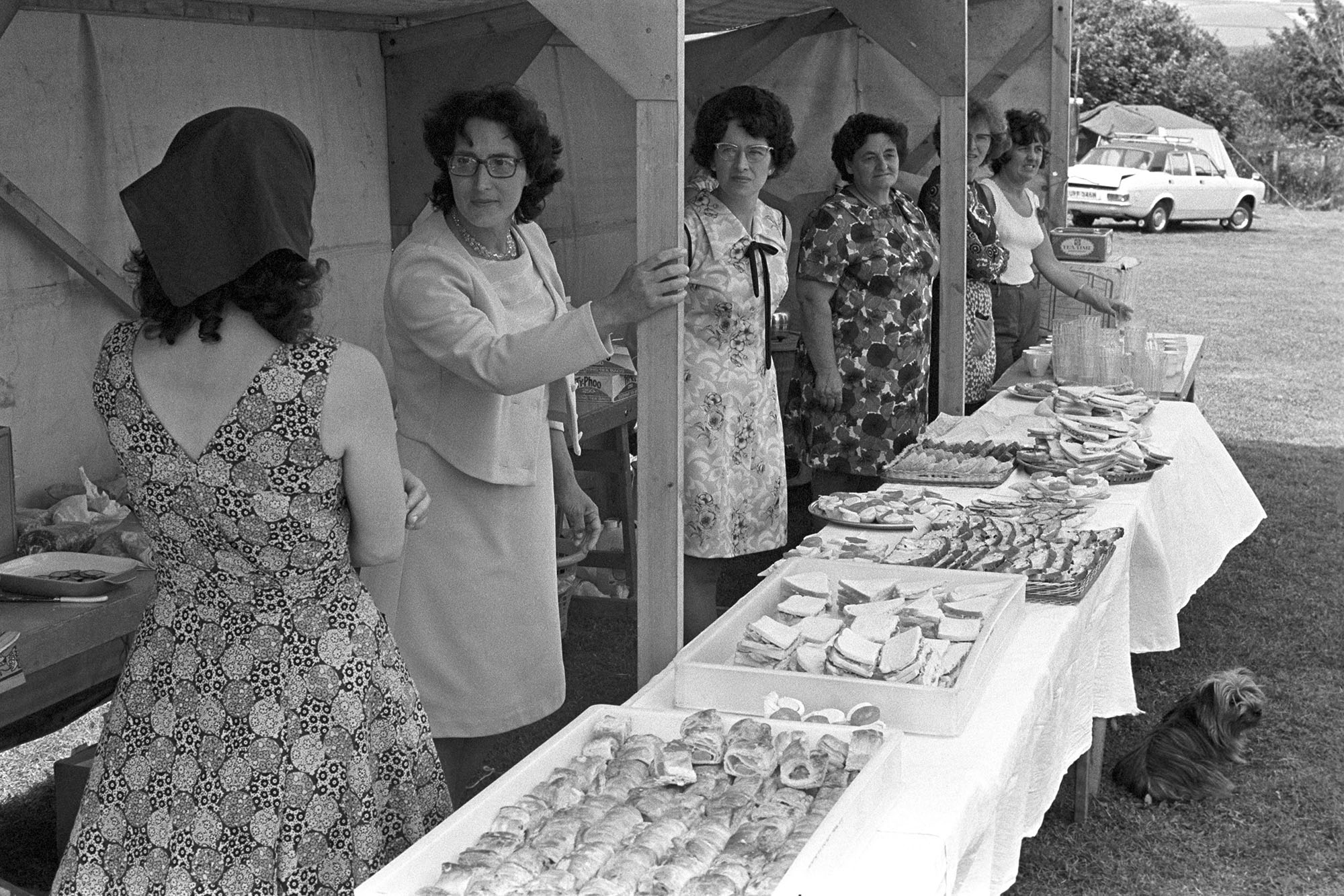 Women at cake stall at fete. <br /> [Six women at a food and refreshments stall, including sausage rolls and sandwiches, at the village fete in Atherington, with a small dog by the table.]