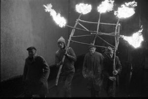 Men carrying a frame of flaming torches at the start of the Carnival by James Ravilious
