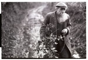 Ivor brock carrying holly for Christmas decorations by James Ravilious