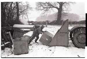 Graham Ward loading a water tank onto a link box by James Ravilious