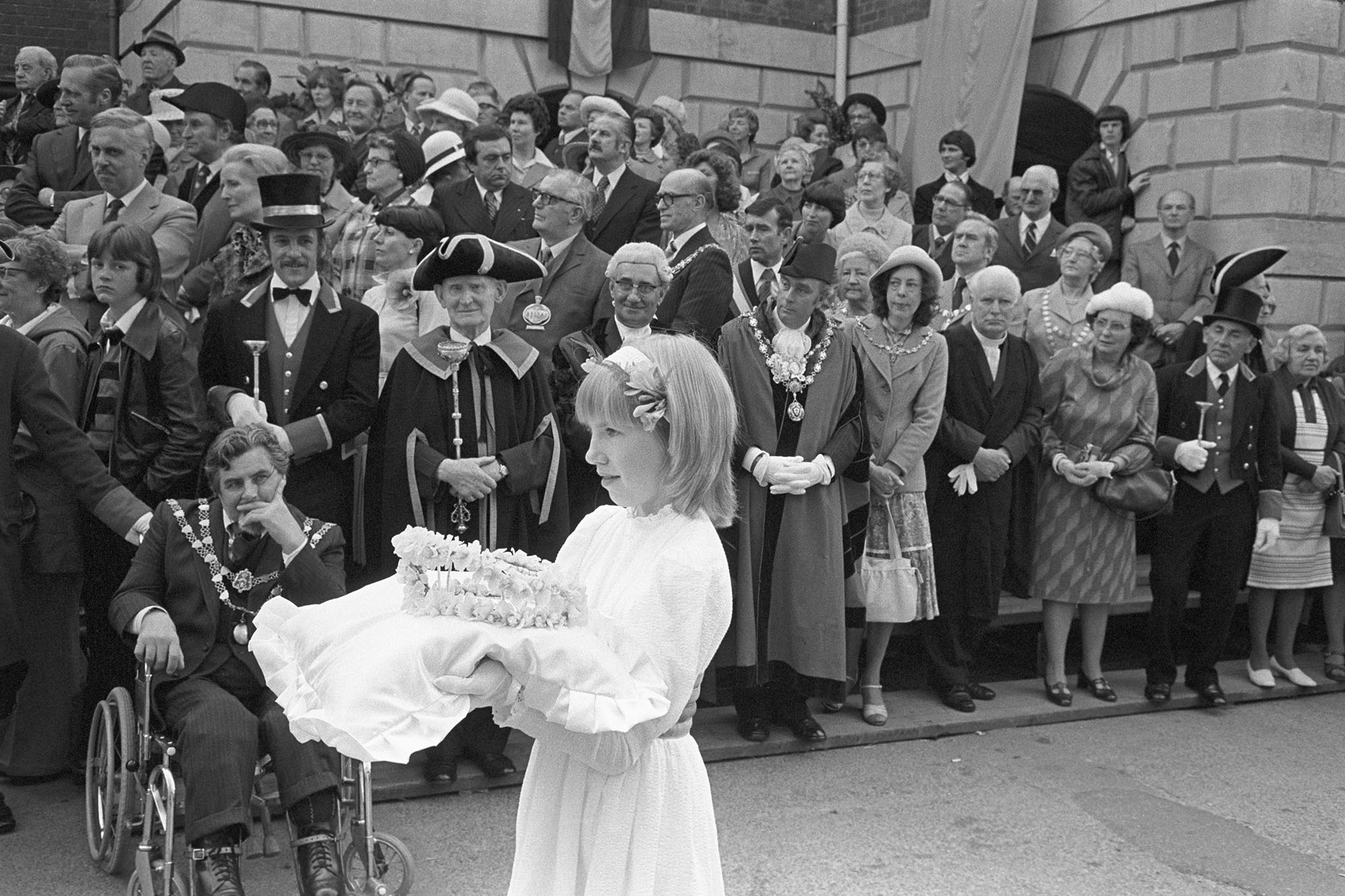 Crowner waiting in front of mayors and dignitaries, holding crown on cushion. <br /> [Tonya Copp walking past Mayors, dignitaries and their wives with the Mayfair crown on a cushion, to crown the May Queen at Torrington Mayfair.]