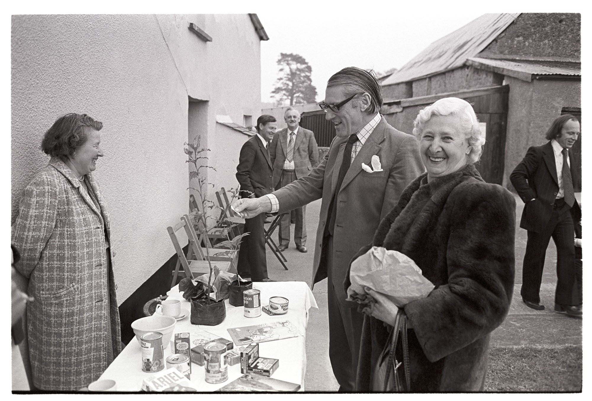 Conservative Party fete at farm, MP and woman at produce stall. <br /> [Peter Mills MP and a woman looking at a plant on a stall at the Conservative Party Fete at great Cudworthy Farm, Dolton.]