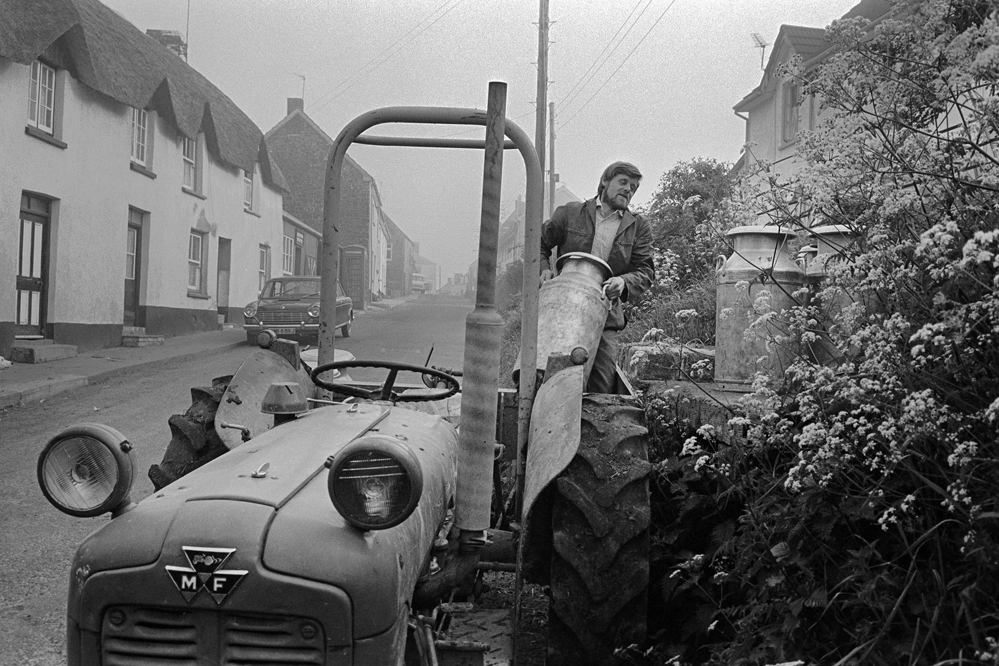 Farmer transferring milk churns to stand in village. <br /> [A man lifting milk churns from his tractor and link box onto a milk churn stand in the village of Sheepwash. Thatched cottages and a parked car are visible in the street.]
