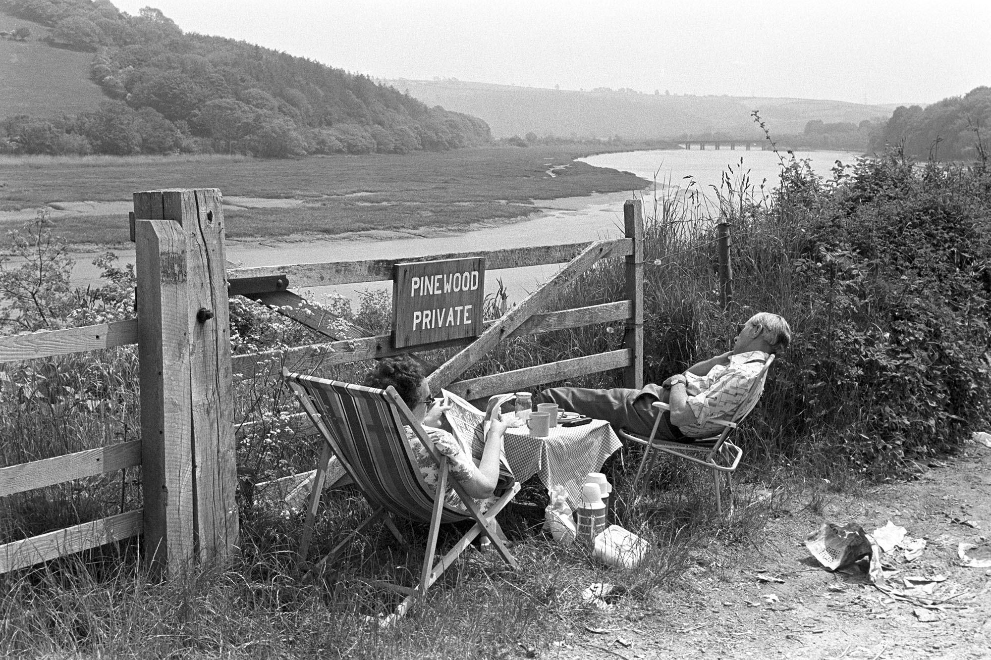 Sleeping tourists after picnic beside estuary. <br /> [Two tourists sat on picnic chairs behind a wooden gate by the river Torridge estuary at Bideford. One is sleeping and the other is reading a newspaper. They also have a small picnic table and thermos flasks.]