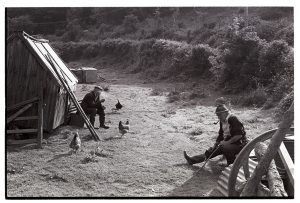 Archie Parkhouse and Ivor Brock chatting beside hen house by James Ravilious
