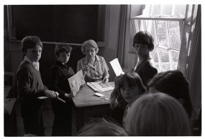 Teacher helping children with their work by James Ravilious