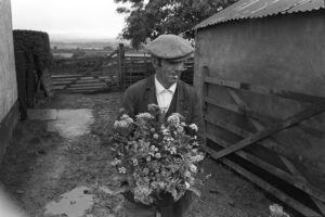 Irwin Piper taking his wife's wildflower arrangement down to the flower show by James Ravilious