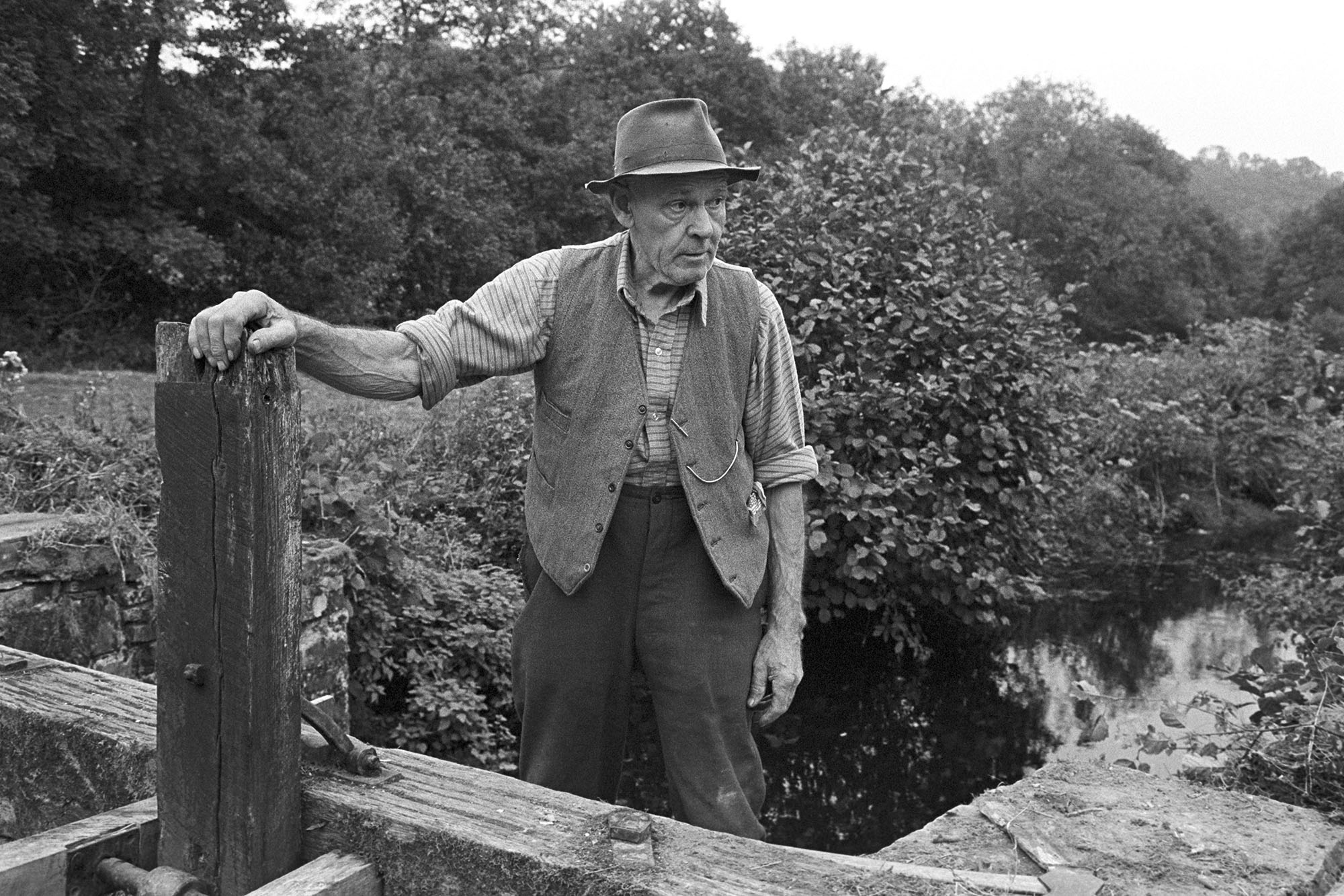 Man, repair of sluice gate of mill leat. <br /> [Herbert Snell stood by a wooden sluice gate he has been repairing on a leat near Head Mill, Kings Nympton.]