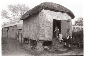 Children entering thatched brick granary by James Ravilious