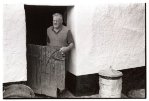 Cyril Bennett at the doorway of the milking shed by James Ravilious