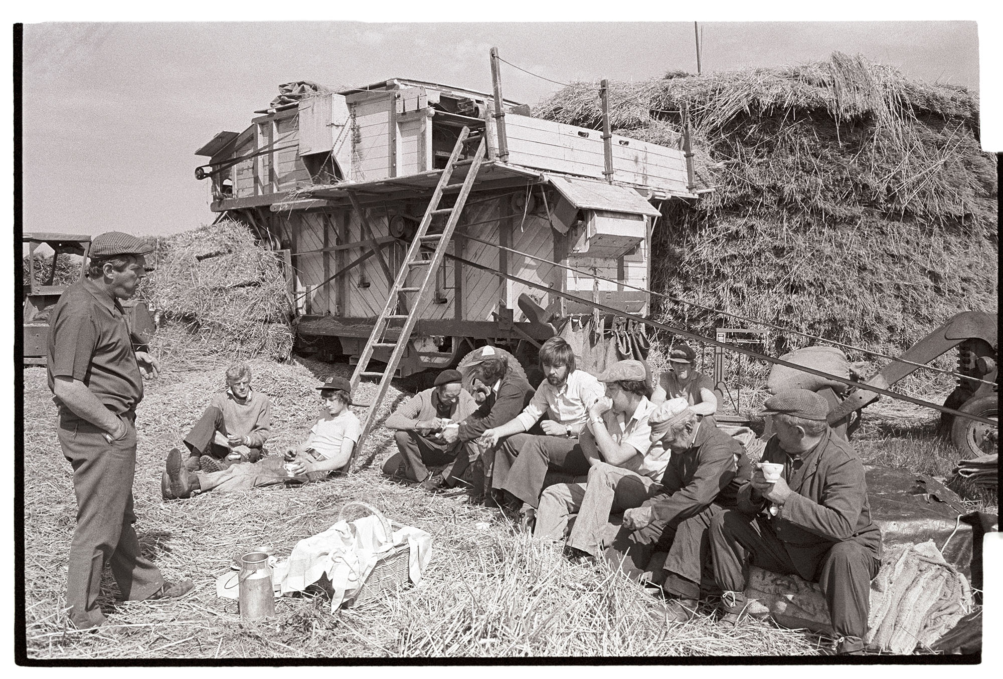 Reed comber's tea break, seated in front of reed comber. <br /> [A group of farm labourers or reed combers sat down in a field of wheat drinking tea at Westacott, Riddlecombe. A flask and picnic hamper is in the foreground, and a reed comber, ladder and wheatrick can be seen in the background.]